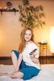 Милая молодая белокурая женщина используя smartphone пока ждущ массаж на курорте стоковая фотография