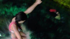 Милая молодая девушка брюнета скача с деревянной платформы в воду системы пещеры Dos Ojos акции видеоматериалы