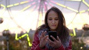 Милая молодая женщина брюнет используя мобильный телефон во время прогулки в замедленном движении на улицах городка ночи с красив видеоматериал