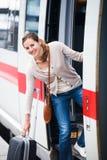 Милая молодая женщина всходя на борт поезда стоковая фотография