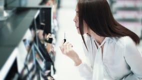 Милая молодая женщина выбирает губную помаду в косметиках ходит по магазинам, пробует ее на губах видеоматериал