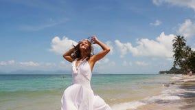Милая молодая женщина в белом венке платья и цветка бежит вдоль берега моря barefoot и наслаждается Пляж с акции видеоматериалы