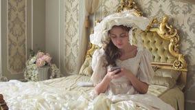 Милая молодая женщина в мантии шарика сидя на кровати и текстах украшенных золотом на сотовом телефоне используя устройство сток-видео