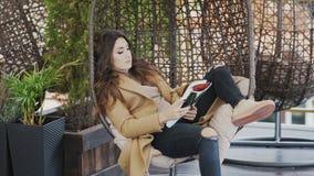 Милая молодая женщина в свитере и пальто сидит в стуле в кафе и читает журнал акции видеоматериалы