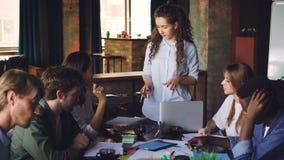 Милая молодая женщина говорит к ее коллегам стоя на таблице пока ее сотрудники смотрят бумаги и делить сток-видео