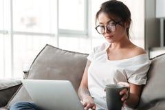 Милая молодая женщина держа чашку кофе используя портативный компьютер Стоковое Фото