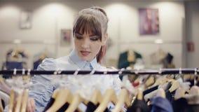 Милая молодая женщина идет шкафом одежд в магазине одежды и принимает быстрому взгляду на одежды сток-видео