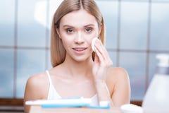 Милая молодая женщина извлекая состав от ее кожи стоковая фотография