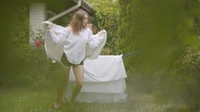 Милая молодая женщина имеет потеху поя и танцуя наслаждающся ритмом на задворк пока делающ работу дома с бельем акции видеоматериалы