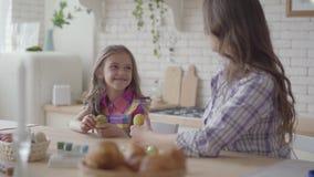 Милая молодая женщина и милая маленькая дочь крася пасхальные яйца с цветами и щеткой Подготовка на праздник пасхи сток-видео
