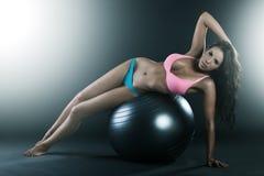 Милая молодая женщина кладя на шарик пригонки, делая разминку стоковое фото rf