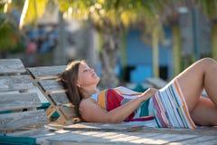Милая молодая женщина лежа на пляже стоковая фотография rf