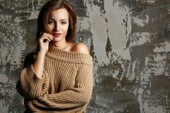 Милая молодая женщина нося связанный свитер с нагим плечом, представляя с тенями Пустой космос стоковое фото
