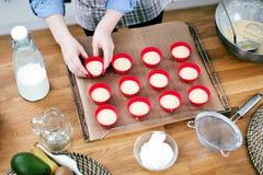 Милая молодая женщина печь вкусные булочки дома стоковая фотография