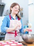 Милая молодая женщина печь вкусные булочки дома стоковое фото rf