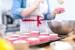 Милая молодая женщина печь вкусные булочки дома стоковые изображения