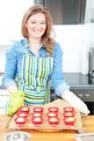 Милая молодая женщина печь вкусные булочки дома стоковое фото