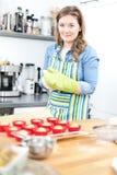 Милая молодая женщина печь вкусные булочки дома стоковое изображение