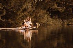Милая молодая женщина сидя озером касаясь воде ее ногой стоковое изображение