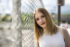 Милая молодая женщина стоя близко загородка звена цепи Стоковая Фотография