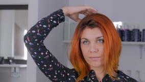 Милая молодая женщина с оранжевым цветом волос на салоне парикмахерских услуг сток-видео
