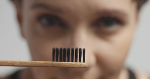 Милая молодая женщина чистя ее зубы щеткой с черной зубной пастой Стоковое Изображение RF