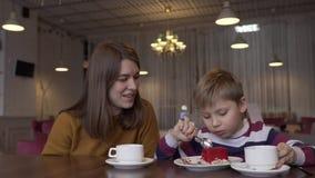 Милая молодая мать и маленький сын есть очень вкусный десерт в кафе сток-видео