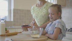 Милая молодая мать и меньший милый повар дочери в кухне совместно E Мама и дочь отношения видеоматериал