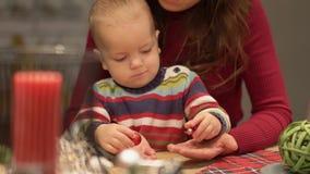 Милая молодая мать и младенец имеют потеху в современной кухне Мама играя с ребенком, закручивая круглой конфетой E акции видеоматериалы