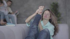 Милая молодая мать сидя на софе с ее лежа сыном Мальчик играя с женщиной с его ногами, дама принимает его сток-видео