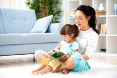 Милая молодая мать читая книгу к ее дочери сидя на ковре на поле в комнате Чтение с детьми стоковые изображения