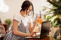 Милая молодая тонкая девушка с темными волосами и стеклами, одетыми в непринужденном стиле, сидит на таблице с ноутбуком в соврем стоковое фото rf