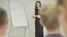 Милая молодая уверенная коммерсантка представляя новый проект к партнерам с диаграммой сальто Руководитель группы давая представл видеоматериал