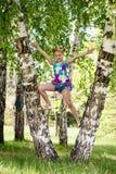 Милая молодая sporty белокурая девушка стоя между 2 деревьями березы, носит купальник спорта colorfull и котелок золота стоковые изображения