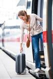 Милая молодая женщина всходя на борт поезда Стоковое фото RF