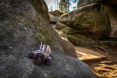 Милая небольшая заполненная зебра игрушки лежа на большом утесе в каменном лабиринте Bledne skaly стоковые изображения rf