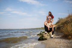 Милая пара подростка датируя на речном береге, красивой девушке и собрате на дате на естественной запачканной предпосылке Стоковое Изображение RF