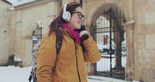 Милая привлекательная кавказская прокалыванная девушка в снежном городе Она слушает музыку на больших белых наушниках Прогулки в сток-видео