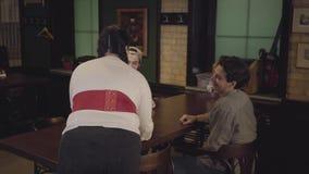 Милая пухлая жирная девушка с 3 стеклами пива на подносе в ресторане пива Официантка приносит пиво до 2 парня к сток-видео