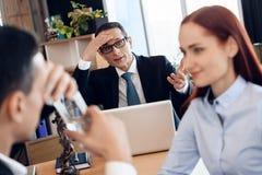 Милая рыжеволосая женщина смотрит человека, выпивая стекла воды в офисе ` s юриста для развода стоковое изображение