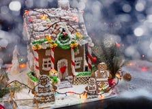 Милая семья пряника около большого покрытого снег дома пряника Стоковое фото RF