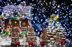 Милая семья пряника с малыми красными подарками приближает к покрытому снег h Стоковое Изображение RF