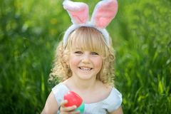 Милая смешная девушка с пасхальными яйцами и ушами зайчика на саде 2 всех пасхального яйца принципиальной схемы цыпленока ведра ц Стоковые Изображения