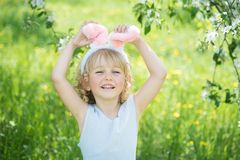 Милая смешная девушка с пасхальными яйцами и ушами зайчика на саде 2 всех пасхального яйца принципиальной схемы цыпленока ведра ц Стоковое фото RF