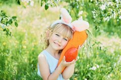 Милая смешная девушка с пасхальными яйцами и ушами зайчика на саде 2 всех пасхального яйца принципиальной схемы цыпленока ведра ц стоковое фото