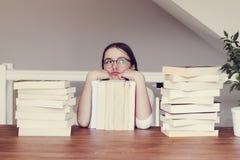 Милая смешная девушка твена в стеклах сидя таблица с кучей книг смотря скептично и daydreaming праздников стоковые изображения rf