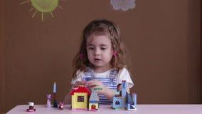 Милая смешная маленькая девочка preschooler играя с игрушкой конструкции преграждает строить башню в комнате детского сада сток-видео