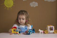 Милая смешная маленькая девочка preschooler играя с игрушкой конструкции преграждает строить башню в комнате детского сада Стоковое фото RF
