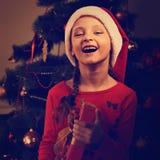 Милая смеясь над девушка ребенк с открытым ртом в рождестве Санта Клаусе Стоковые Фото