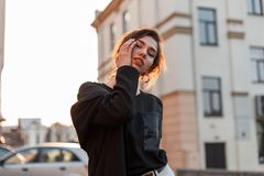 Милая современная стильная молодая женщина с естественным макияжем с сексуальными губами в модной футболке в ультрамодном пальто стоковая фотография rf